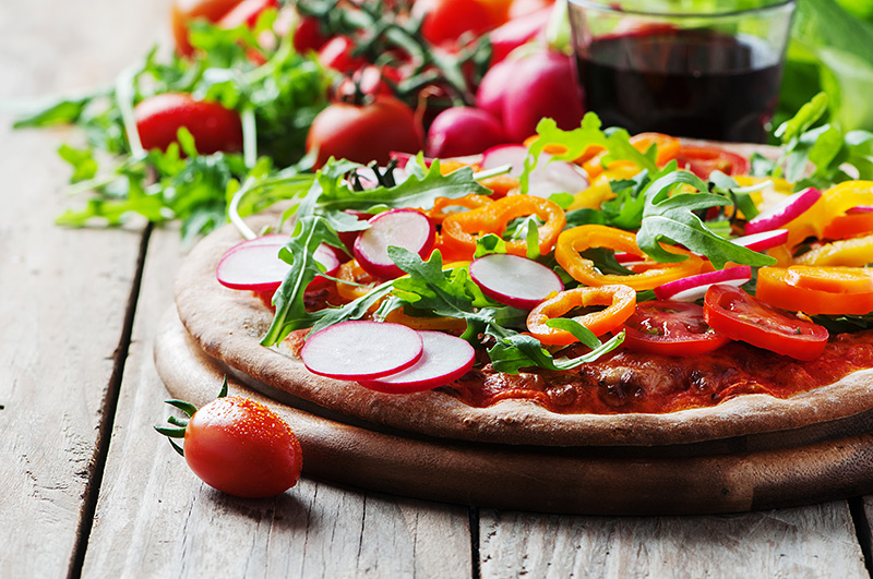 Vegan pizza with radish, tomato and paprika, selective focus
