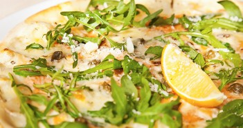 Pizza with arugula, capers, parmesan and lemon